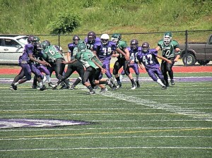 Alfred MacIntosh (74) and Jesus Ochoa (47) pursue the ball carrier /  Photo by Roger Starkey