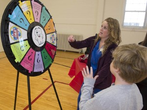 """SIUE dental student Kasey Kirchner has fun with a young contestant, challenging the """"Circle of Smiles,"""" a spinning wheel that offered oral health education and fun, at the Smile Station during the 2012 Give Kids A Smile Day."""