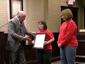Mayor John Miller presents the Karrie Brown Day proclamation to Karrie Brown. With Sue Brown, Karrie's mother, far right