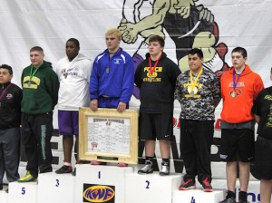 Alfred McIntosh (white shirt) on the podium after winning 3rd place at the IKWF Wrestling State Tournament / submitted photo
