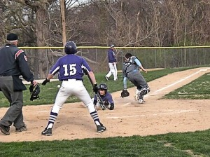 Grant Bauer slides home safely, as Kyle Reeves notes / Photo by Roger Starkey