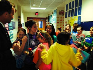 Rick Kincheloe, of Edward Jones, watches as Stephanie Ralston is embraced by a throng of adoring students after being presented with the Unit 10 Teacher of the Month award for Apri, 2014 / Photo by Laura Bauer