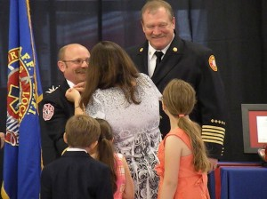 Tim Rainey being pinned by his wife while Fire Chief Mark Emert shares a laugh with Rainey's oldest daughter / Photo by Roger Starkey