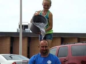 DIS 5th grader Taylor Murphy dumps ice water on the head of DIS Principal Kevin Stirnaman / Photo by Roger Starkey