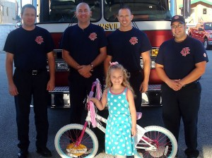 Aurora Perigo stands with her new bike, along with members of the Collinsville Fire Department / Submitted photo