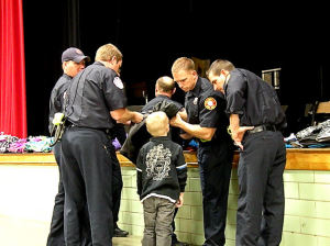 Collinsville firefighters help a Webster Elementary School student choose a coat. The firefighters are giving away 50 coats to the neediest Collinsville Unit 10 students / Photo by Roger Starkey