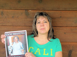 Robin Burton holds a picture of her missing mother, Cloudia Leslie Wells / Photo by Roger Starkey