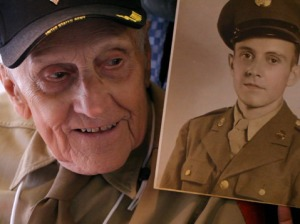 "A World War II veteran brings along a photo of himself as a soldier in his youth. His volunteer travel companion, or ""guardian,"" holds the picture up for him on their flight to Washington, DC. / Photo courtesy of Freethink Media"