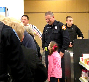 A Collinsville firefighters speaks with a young girl Dec. 10 as she checks out at Wal-Mart in Colllinsville / Photo by Roger Starkey